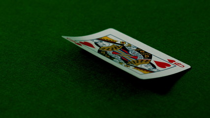 Queen of hearts falling on casino table