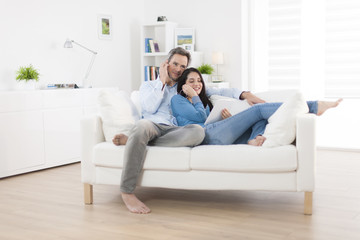 cheerful couple sharing music on digital tablet in sofa at home