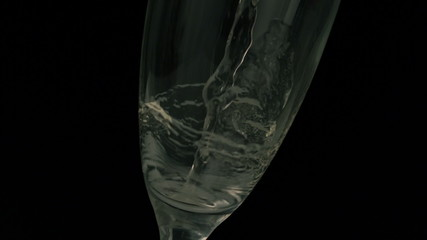 Champagne pouring into flute on black background