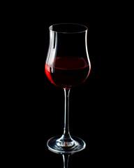 Rotweinglas vor schwarzem Hintergrund