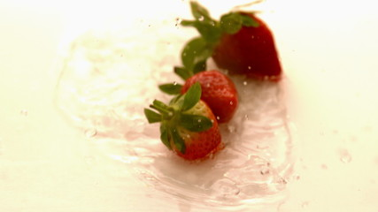 Strawberries falling on white wet surface