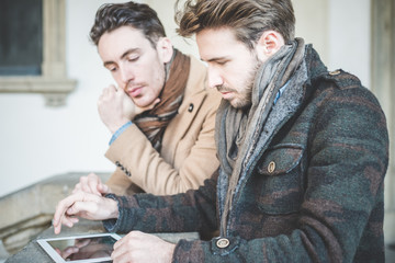 two young handsome businessmen using tablet