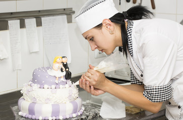 pastry chef decorates a cake in a candy store