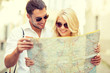 smiling couple in sunglasses with map in the city
