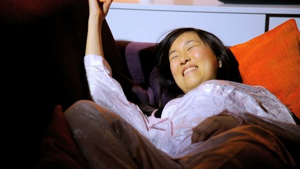 Asian woman relaxed at home falling asleep on couch