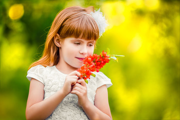 Portrait of a little girl outdoor in a garden smelling the flowe