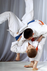 Boys in judogi are training throwing