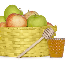 Rosh Hashana basket of apples, glass jar of honey, wood stick