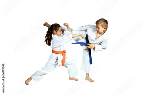 Fotobehang Vechtsporten Girl and boy in karategi are training paired exercises karate