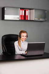 Portrait of smiling beautiful young support phone operator in