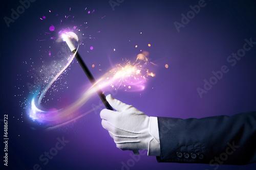 Leinwanddruck Bild High contrast image of magician hand with magic wand