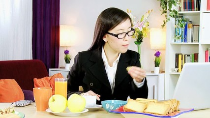 Asian student at home working during breakfast