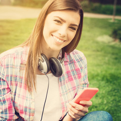 Young woman with headphones and phone in park in summer