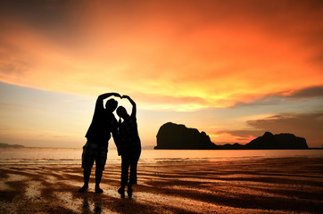 Romantic couple holding hands at sunset on beach