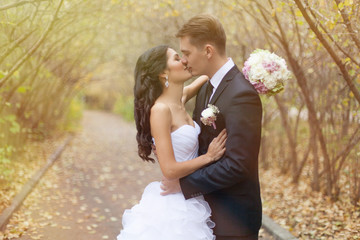 Newlyweds embracing each other smiling at camera in the countrys