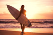 Silhouette surfer girl on the beach at sunset