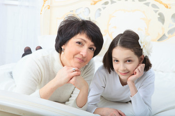 Mother and daughter lying in bed smiling to camera