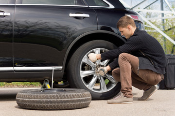 Young man changing the punctured tyre on his car