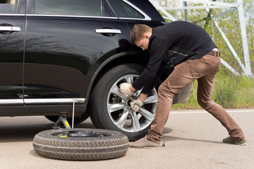 Young man struggling to change his car tyre