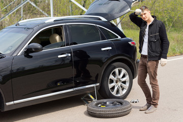 Male driver changing his car tyre after a puncture