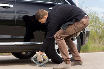 Man placing a hydraulic jack under his car