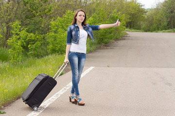 Young woman holding a trolley while hitchhiking