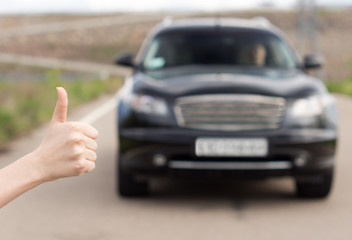 Woman giving a thumbs up as she stands hitchhiking