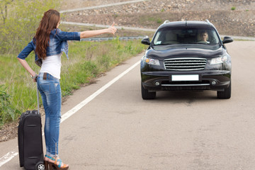 Trendy woman hitchhiking on a country road