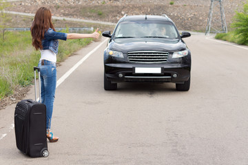Young woman hitchhiking with a suitcase