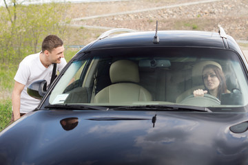 Young man chatting up a female driver