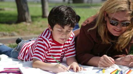 Mother and son painting in the park