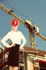 Female engineer woman in red safety helmet on construction site