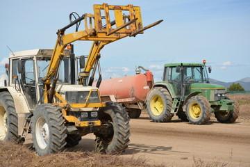 dos tractores trabajando en una carretera en construccion