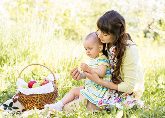 baby and mom sit with basket outdoors