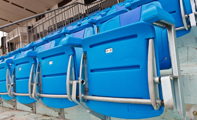 Blue empty plastic seats at stadium