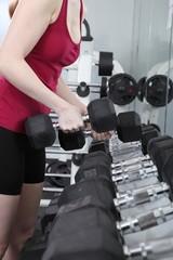 Junge Frau trainiert im Fitnessstudio mit Hanteln