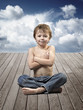 Portrait of a beautiful young boy sitting in yoga pose on a wood