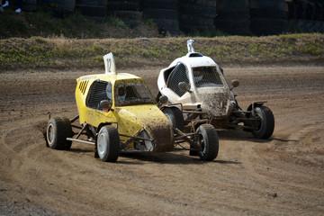 dos buggies adelantandose en una curva de carrera