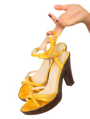 Close up portrait of a female hand holding yellow shoe , isolate