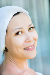 Close up portrait of young smiling woman with a towel hat