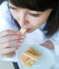Close-up  portrait of young women eating the sweet waffles
