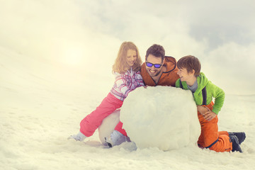 father and his son and doughter building a snowman