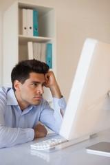 Casual businessman slumped at his desk