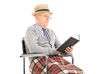 Senior man reading a book seated in wheelchair