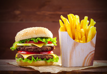 Hamburger with fries on wood