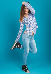 beautiful girl in a shirt and jeans posing