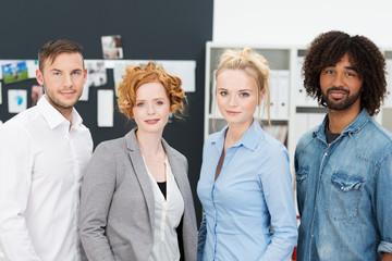 vier junge kollegen stehen im büro