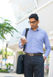 Young Indian Businessman using a smart phone standing outside a