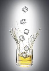 Splashing juice in glass. Isolated on white background