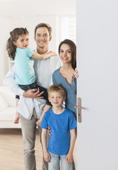 Family standing at front door to invite people at home